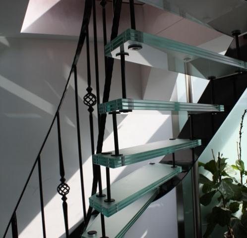 glazen trap met smeedijzersen trapbalustrade